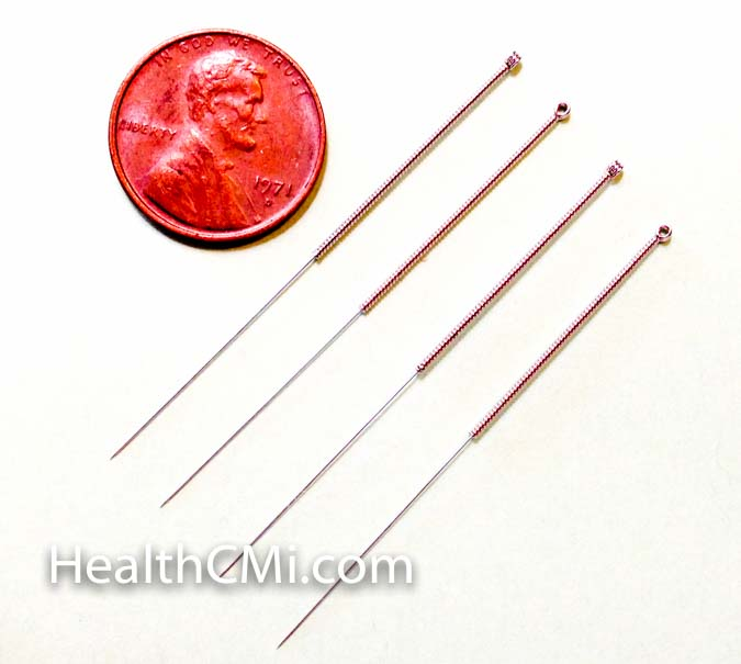 Four filiform needles against size of a penny